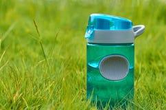 La bottiglia di plastica di sport sta in un campo su un'erba verde Immagini Stock Libere da Diritti
