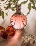 La bottiglia di profumo rosa sui precedenti di legno della natura Immagine Stock Libera da Diritti