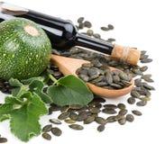 La bottiglia di vetro dell'olio del seme di zucca, la zucca e la zucca sbucciata vedono Fotografia Stock Libera da Diritti