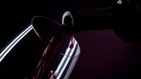 La bottiglia di vino, il vino è versata in un vetro, il nero, il primo piano, rallentatore video d archivio