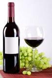 La bottiglia ed il vetro di vino rosso e dell'uva dentro appoggiano immagini stock libere da diritti