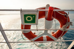 La bouée de sauvetage avec se connectent une barrière de ferry, avec le soleil et la mer dans le backgro Photos libres de droits