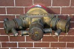 La bouche d'incendie avec des tuyaux de l'eau et le feu s'éteignent l'équipement sur la brique Image libre de droits
