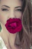 La bouche de dissimulation de jeune belle femme avec s'est levée Photographie stock