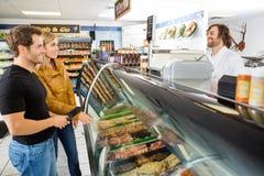 La boucherie d'Attending Customers At de vendeur photo stock