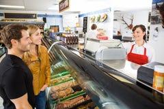 La boucherie d'Attending Customers At de vendeuse photos stock