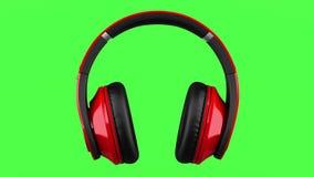 La boucle sans fil rouge et noire d'écouteurs tournent sur le chromakey vert banque de vidéos