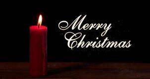 La bougie brûle sur la table avec le texte de Joyeux Noël banque de vidéos