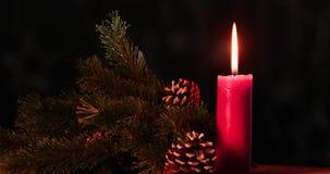 La bougie de Noël brûle sur la table avec des cônes de pin banque de vidéos