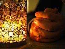 La bougie et les mains se sont pliées ensemble dans la prière ou la pétition images stock