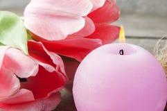 La bougie et les tulipes roses d'arome se ferment  Photographie stock libre de droits