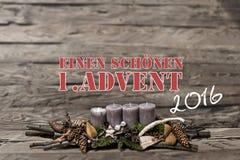 La bougie grise brûlante de l'avènement 2016 de décoration de Joyeux Noël a brouillé l'Allemand 1er de message textuel de fond Image stock