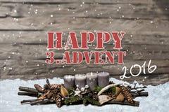 La bougie grise brûlante de l'avènement 2016 de décoration de Joyeux Noël a brouillé l'englisch 3ème de message textuel de neige  Photos stock