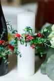 La bougie l'épousant blanche large décorée par un rouge fleurit et gre Photographie stock