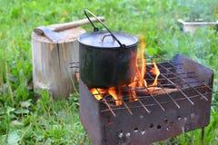 La bouilloire avec un aliment sur un brasero Photos stock