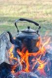 La bouilloire se tient sur un feu ouvert, récréation extérieure photographie stock libre de droits