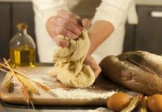 La boulangère de femme remet, malaxe la pâte et les travaux domestiques de fabrication faisant le pain, beurre, farine de tomate image libre de droits