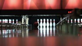 La boule casse des goupilles de bowling L'homme joue le mouvement lent de roulement Le jeune homme assomme la grève banque de vidéos