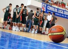 La boule de basket-ball décrite avec une équipe a recueilli autour de l'entraîneur à l'arrière-plan Photographie stock libre de droits