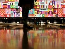 La boule de la fille frappe des goupilles de bowling à un bowling photographie stock libre de droits