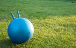 La boule de forme physique s'étend sur une herbe Photo stock