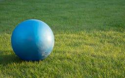 La boule de forme physique s'étend sur une herbe Photographie stock