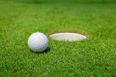 La boule de golf se trouve sur le vert Image libre de droits