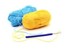 La boule de laine et le crochet de crochet jaunes et bleus sur le blanc ont isolé le CCB Photos libres de droits