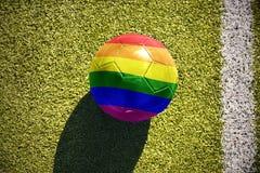 La boule du football avec le drapeau gai d'arc-en-ciel se trouve sur le champ Photo libre de droits