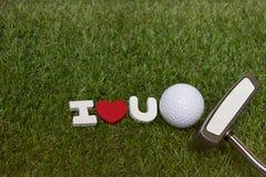 La boule et le putter de golf avec se connectent je t'aime le cours vert Photos stock
