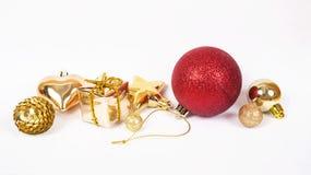 La boule rouge avec d'autres babioles de Noël aiment la décoration de vacances sur le blanc Image libre de droits