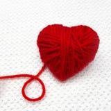 La boule rouge de fil comme un coeur et un fil font une boucle sur le fond blanc de crochet Concept romantique de jour de Noël ou Images libres de droits