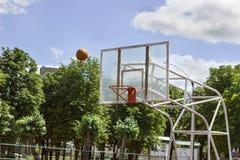 La boule vole dans l'anneau de basket-ball un temps ensoleillé et clair Photo stock