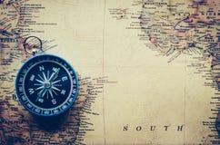 La boussole bleue est placée sur la carte du monde Photographie stock