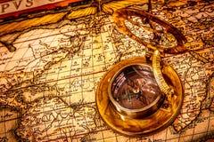 La boussole de vintage se trouve sur une carte antique du monde. Photo libre de droits