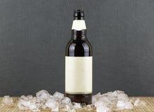La bouteille à bière sur la table avec de la glace rapièce Photographie stock libre de droits