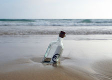 La bouteille avec l'euro se connectent le sable de la plage Image libre de droits