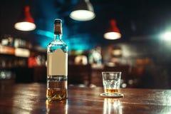 La bouteille d'alcool et le verre sur la barre parent le plan rapproché image libre de droits