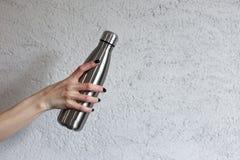La bouteille d'eau thermique en acier dans la main de fille sur le fond disparaissent mur gris photos stock