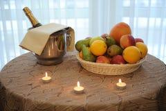 La bouteille de champagne dans un plateau de seau et de fruit a servi sur la table avec des bougies Image stock