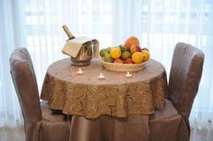 La bouteille de champagne dans un plateau de seau et de fruit a servi sur la table avec des bougies Photo stock