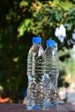 La bouteille de l'eau 1,5 litres et une moitié sur le fond bleu avec de l'eau bleu teinte bleuâtre se laisse tomber Photographie stock libre de droits