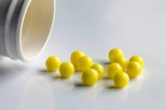 La bouteille de pilule de prescription renversant des pilules dessus sur la surface a isolé o Photographie stock