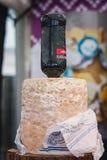 La bouteille de port a collé dans un fromage de stilton montré sur la nourriture f image libre de droits
