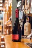 La bouteille de vin noir, verdissent avec le label et le chapeau rouges dans le magasin de vin images libres de droits