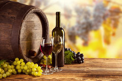 La bouteille et le verre de vin rouge et blanc wodden dessus le barillet Image stock