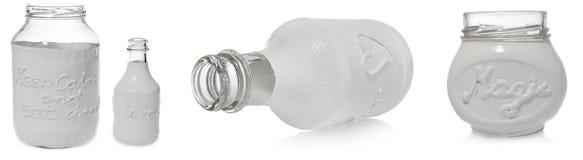 La bouteille vide blanche peinte avec amour d'inscription et le pot blanc avec l'inscription gardent le calme et mangent le choco Images stock