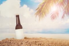 La bouteille vide de Logo Beer dans poncent avec le fond de plage photos stock