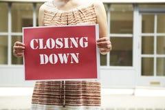 La boutique vide d'extérieur debout de femme jugeant fermante signent vers le bas Photographie stock