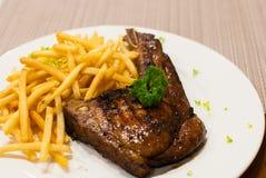 La braciola di maiale ha grigliato la bistecca con le patate fritte, cima con prezzemolo. Immagini Stock Libere da Diritti
